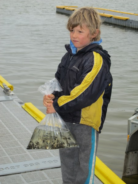 Young lad with a demo bag of fingerlings